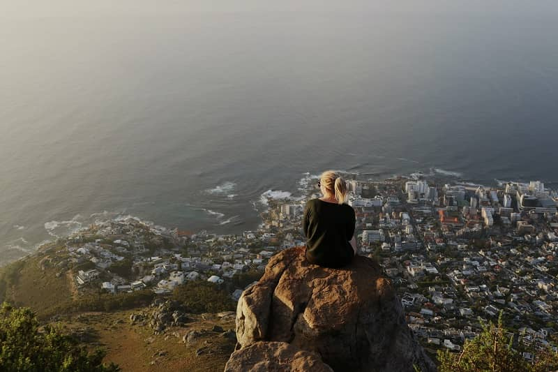 A female traveler sitting at Lion's Head, Cape Town, South Africa